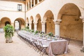 wedding reception courtyard italy destination wedding reception low centerpiece arch pillars bistro