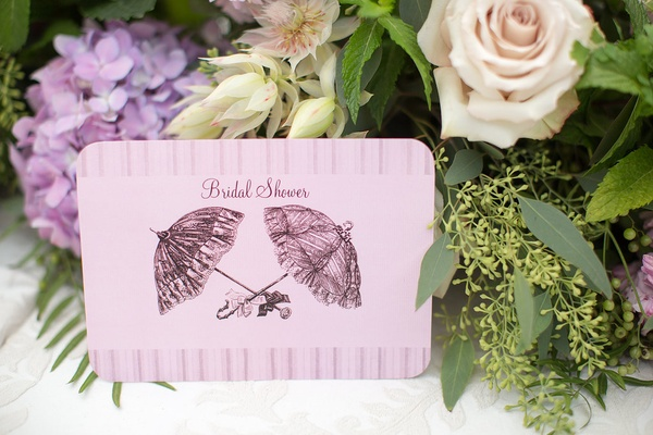 pink bridal shower invitation with parasol umbrella sketch motif on front