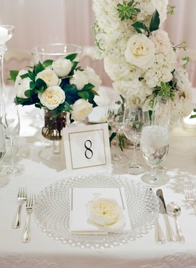 Cut crystal charger plate at wedding white table linen white rose hydrangea flower arrangement