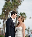 Groom in white bow tie suit and bride in Ines Di Santo wedding dress lace illusion strapless