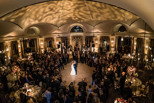 Wedding guests surrounding dance floor at Pleasantdale Chateau wedding venue spotlight on couple