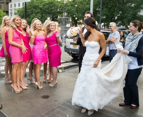 Bride walking in NYC street waves to bridesmaids
