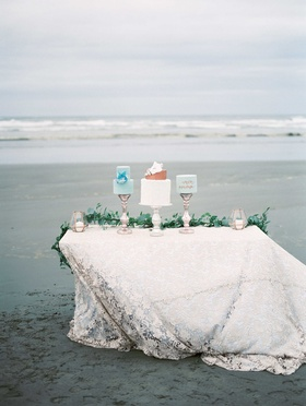three different cakes on top of a white linen table with a green garland runner on a beach