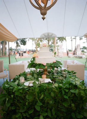 wedding reception tent chandelier over cake three layer fresh flowers green leaves covering table