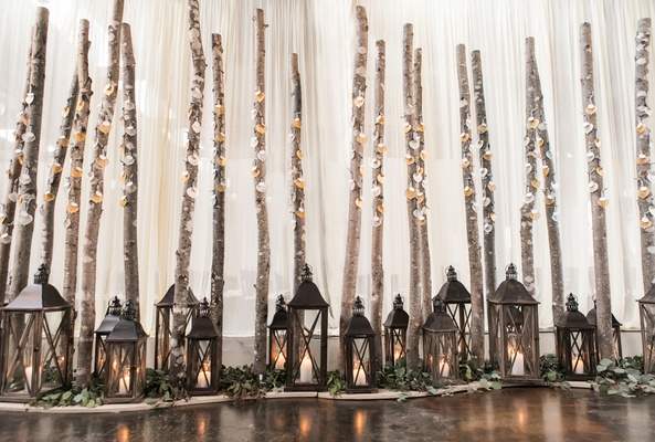 rustic escort card display with lanterns and branches
