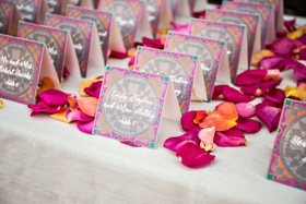 wedding reception escort card table pink orange flower petals pink orange grey green escort cards