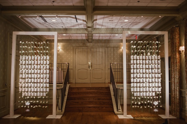 escort cards on calla lilies on lucite wall
