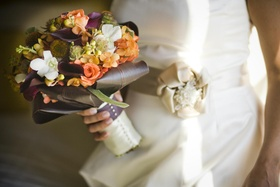 Bride holding purple, green, and orange autumn flowers