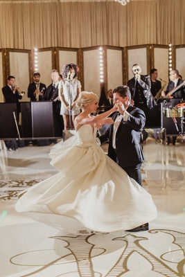 bride in isabelle armstrong wedding dress dancing and twirling with groom monogram white gold