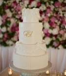 White wedding cake with classic piping and gold monogram
