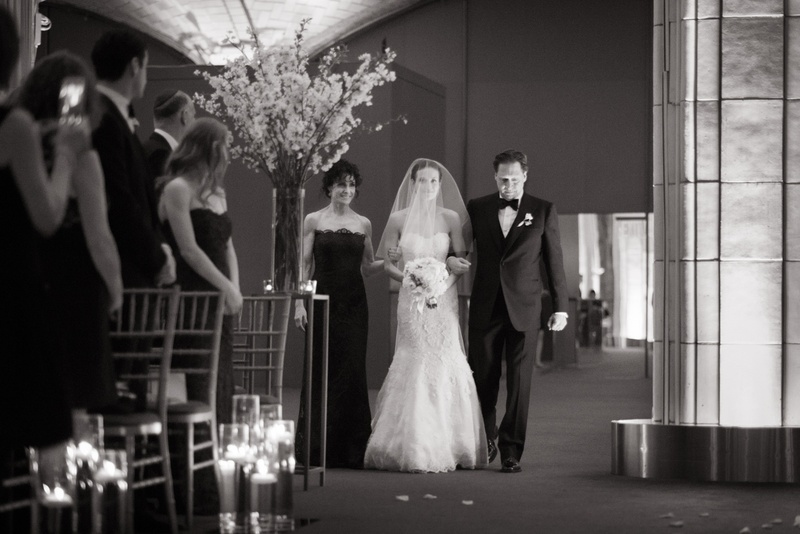 black and white photo of a bride walking down the aisle lead by her parents