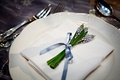 Wedding reception place setting is decorated with a small bundle of flowers