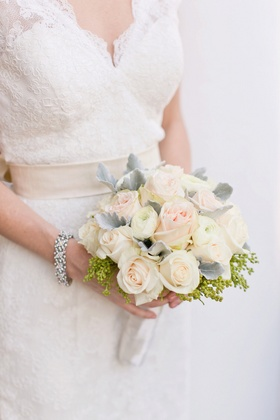 Bride in a lace Watters dress with bouquet of white ranunculus, light pink roses, dusty miller