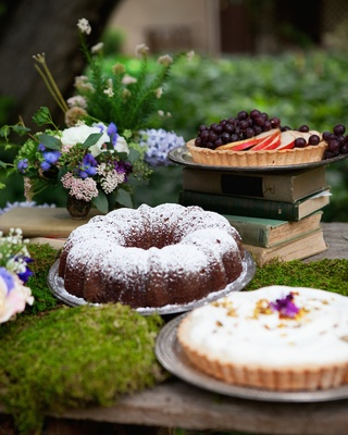 A fruit tart on stack of books, bundt cake, and cream pie at outdoor wedding reception