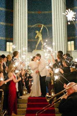 Bride in fur stole wrap kissing groom in white tuxedo jacket sparkler exit red carpet hall of state