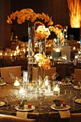 Wedding reception table with three cylinder vases with orchid stems surrounded by candles