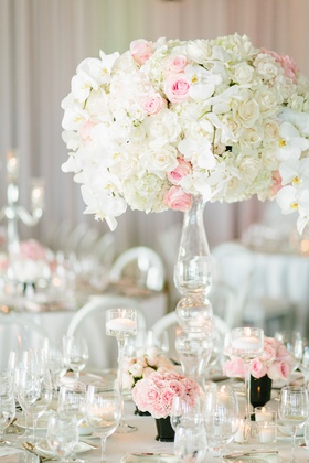 wedding reception centerpiece with ivory roses, pink roses, and white orchids