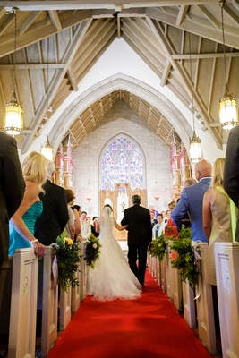Bride holding arm of father of bride down red carpet aisle runner church ceremony stained glass