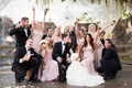 bridesmaids in amsale, bride in vera wang, bridal party celebrates as newlyweds kiss