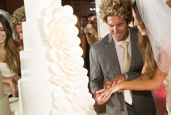 Bride and groom cut all-white wedding cake