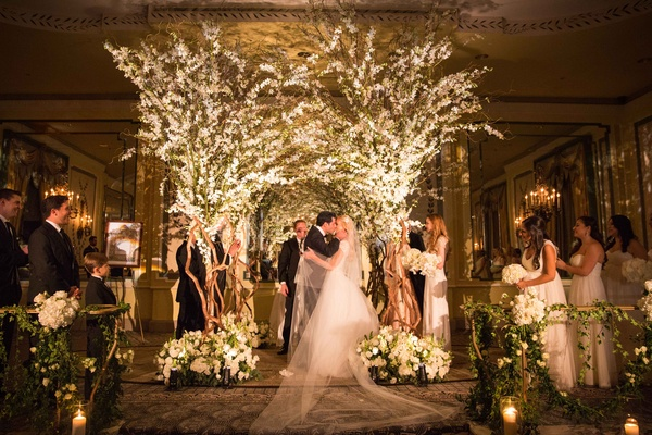 bride and groom share first kiss under chuppah looks like trees with branches foliage white flowers