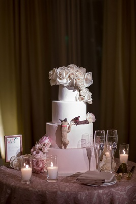 wedding cake with white blush layers fresh flowers and dog replica eating cake
