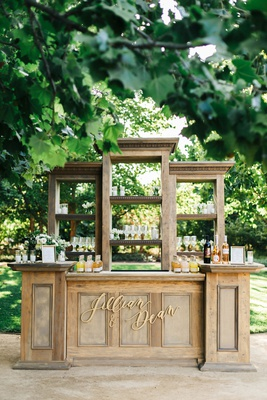 Jillian Murray and Dean Geyer outdoor wedding reception wood bar gold calligraphy sign names shelves