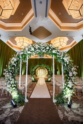 wedding ceremony ballroom circle arch flowers greenery white flower ropes  white aisle chairs