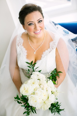 bride in v neck wedding dress lace pretty necklace earrings white bouquet eyeliner pink lipstick