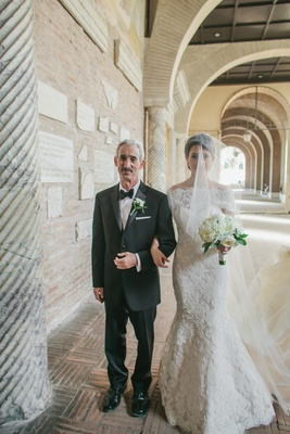 dad wearing black tuxedo walks daughter in lace dress down corridor
