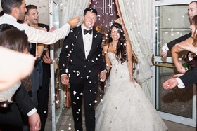 newlyweds exit guests throw confetti on them trumpet wedding gown black tuxedo