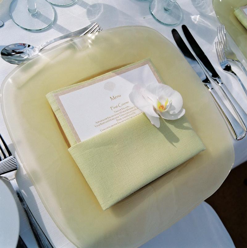 Pale yellow plate, linen napkin, and shell motif menu
