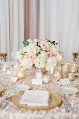 Textured linens with gold charger plate, candle votives, and low flower arrangement centerpieces