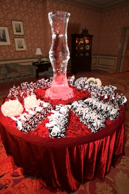 Wedding favor table with ice sculpture, red velvet tablecloth, and rose petals