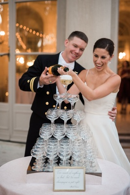 Bride and groom pouring champagne into tower of glasses coupe glass military wedding reception