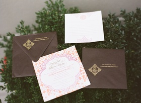 Brown and gold envelopes with orange and pink wedding invite