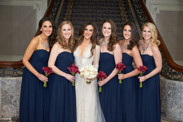Bridesmaids in strapless navy blue dresses with calla lily bouquets bride Inbal Dror wedding dress