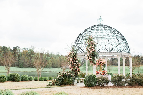 2400 on the river wedding, gazebo with white columns with large flower arrangements