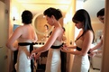 Bridesmaids in strapless cream gowns with black sashes