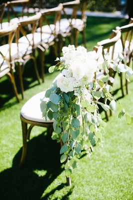 wedding ceremony grass lawn wood chair with greenery and white rose flowers on aisle decoration