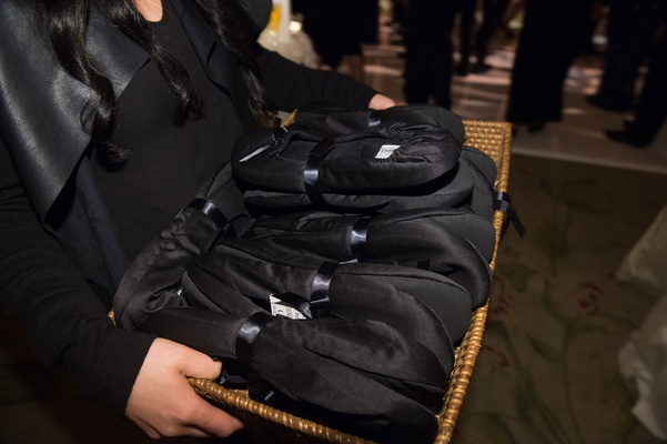Server carrying around basket of black satin flat shoe slippers for dancing at wedding reception