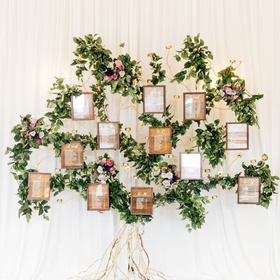 wedding reception seating chart wood grain alphabetical on gold structure with greenery purple bloom