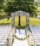 Wedding ceremony outside white aisle runner shepherd hook flower garland flowers along aisle arch
