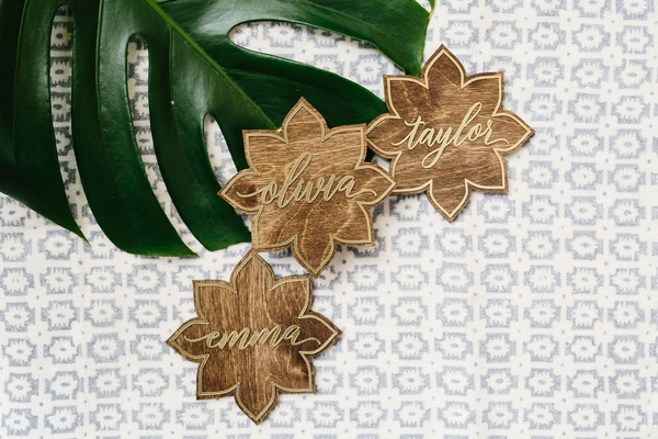 wedding moroccan style theme wood walnut escort cards flower shape gold calligraphy
