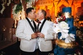 two grooms in white tuxedo jackets with black lapels kiss next to tall blue wedding cake