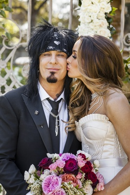 Bride kissing Mötley Crüe groom on cheek