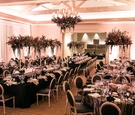 modern wedding reception with black linens, black chairs, dark purple florals, king's tables