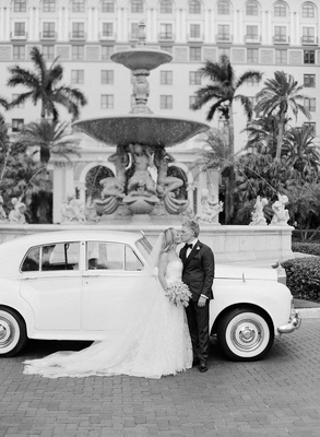 Black and white photo of bride and groom in front of classic white car in front of the breakers