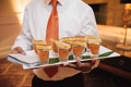 Server tray passing tomato soup in shot glasses with mini grilled cheese sandwiches on top
