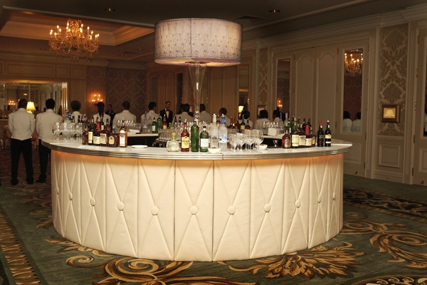 Wedding reception in a ballroom with a white bar